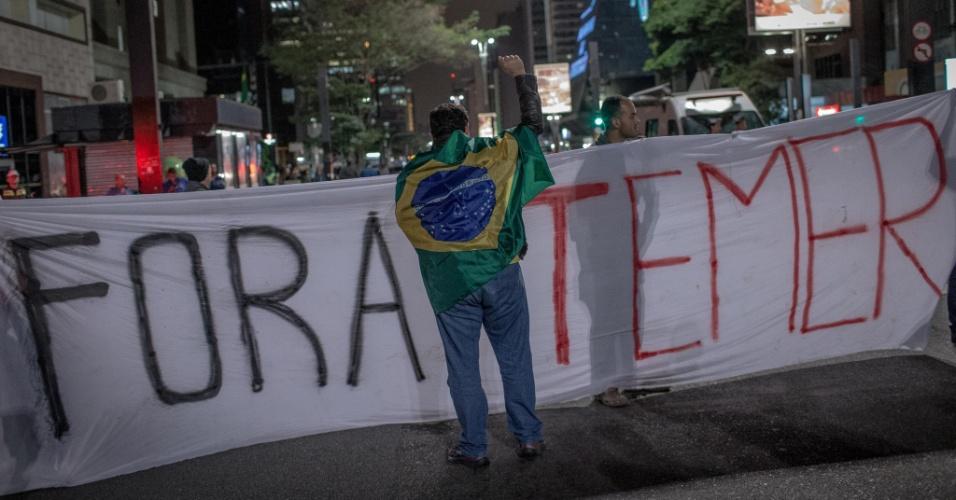 17.mai.2017 - Homem, enrolado com a bandeira do Brasil, manifesta-se contrário ao presidente Michel Temer, na avenida Paulista
