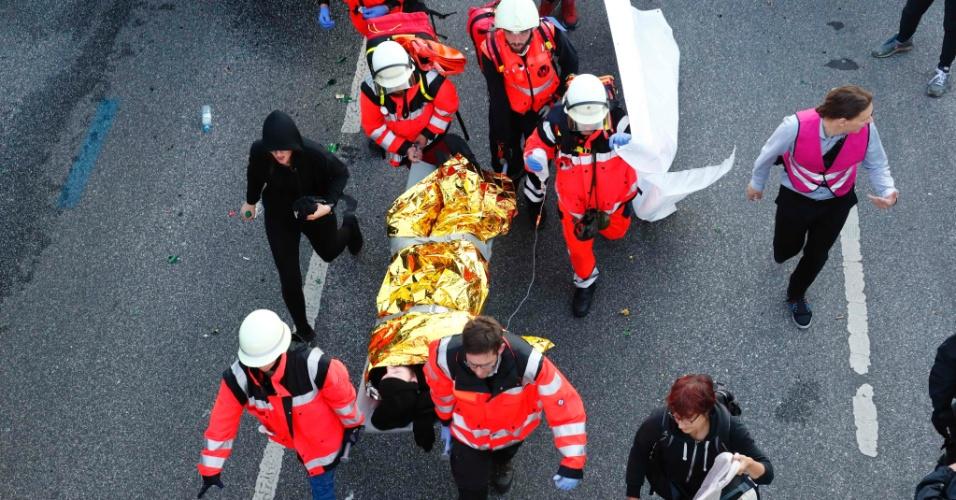 6.jul.2017 - Manifestante ferido é socorrido durante protesto contra cúpula do G20 em Hamburgo, na Alemanha