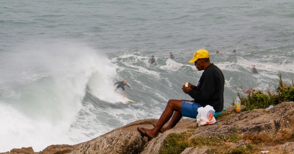 12.ago.2017 - Surfistas aproveitam a ressaca, enquanto homem se alimenta vendo a paisagem