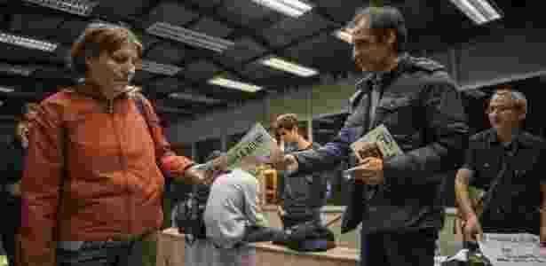 Voluntário de extrema-direita distribui jornal pedindo voto contra o casamento gay em estação de metrô de Bucareste, capital da Romênia - Daniel Mihalescu/AFP Photo
