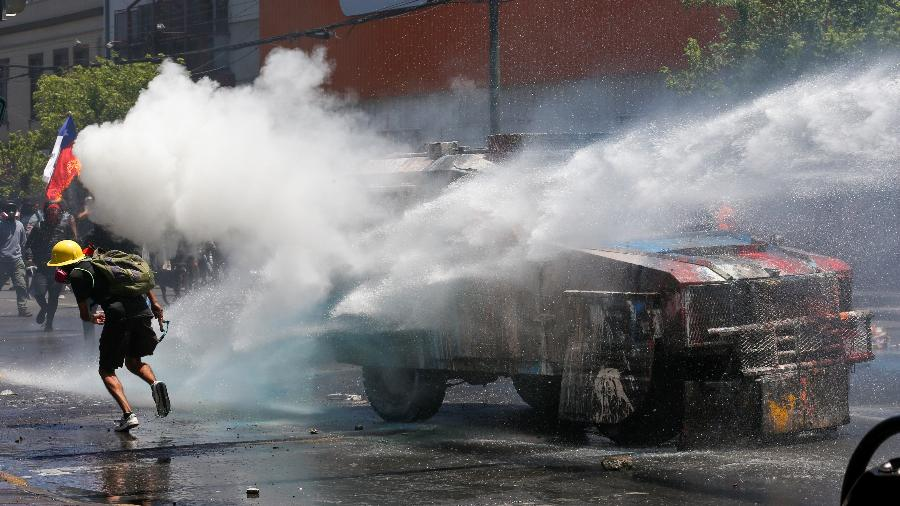 Manifestante é alvo de jatos de água durante protestos em Valparaíso contra o governo chileno - Rodrigo Garrido/Reuters