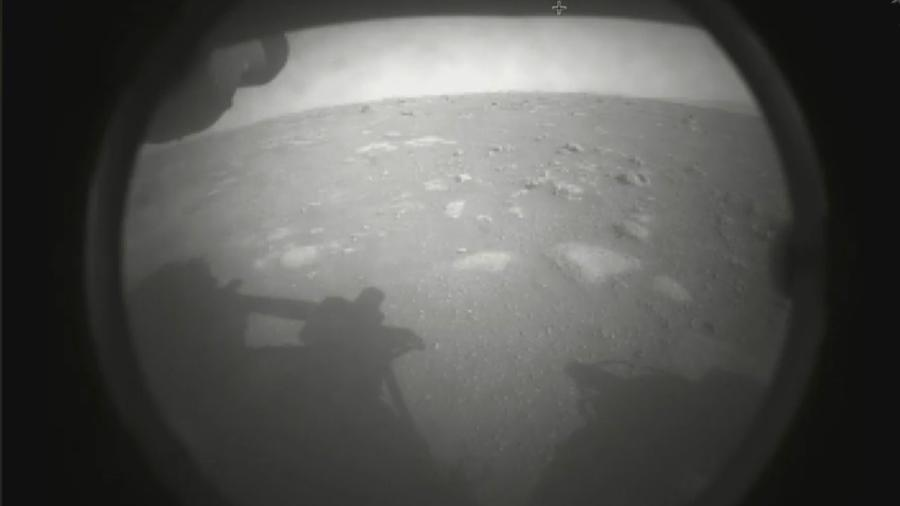 """A primeira imagem de Marte fornecida pelo Perseverance chegou pouco depois do pouso e mostra a sombra de um dos """"braços"""" do robô - Divulgação/Nasa"""