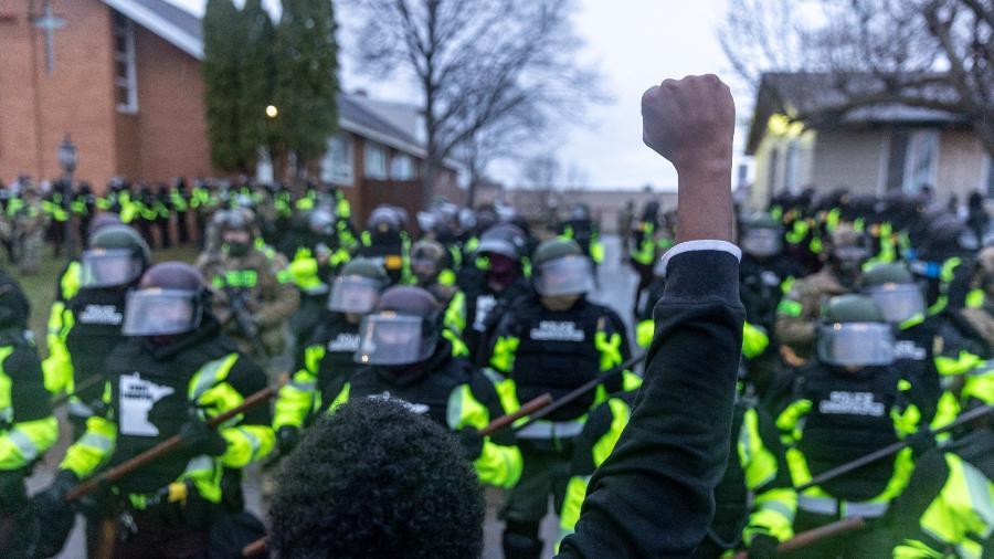 12.abr.2021 - Homem levanta o punho em frente aos policiais de Minnesota que montam guarda do lado de fora da delegacia do Brooklyn Center depois que um policial atirou e matou Daunte Wright - Kerem Yucel/AFP