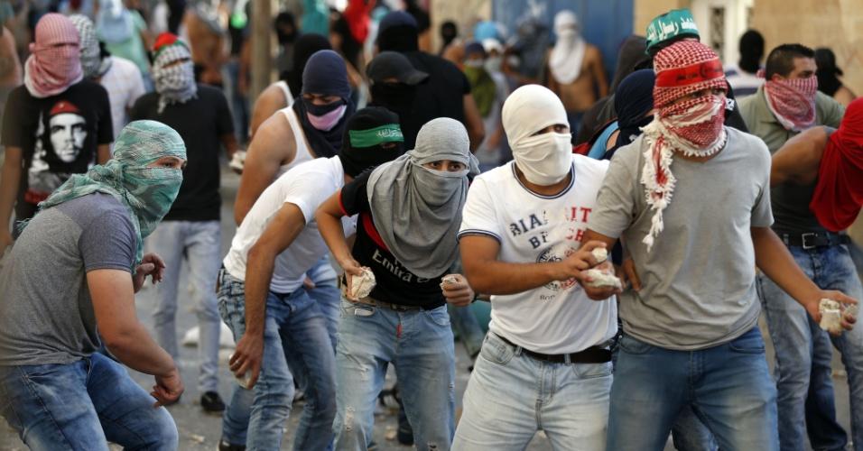 5.out.2015 - Manifestantes palestinos atiram pedras durante confronto com forças israelenses no bairro palestino de Shuafat, em Jerusalém Oriental. A cidade e a Cisjordânia têm vivido uma escalada de violência nas ruas após o assassinato de quatro israelenses por palestinos e a morte de dois jovens palestinos na Cisjordânia por tropas de Israel