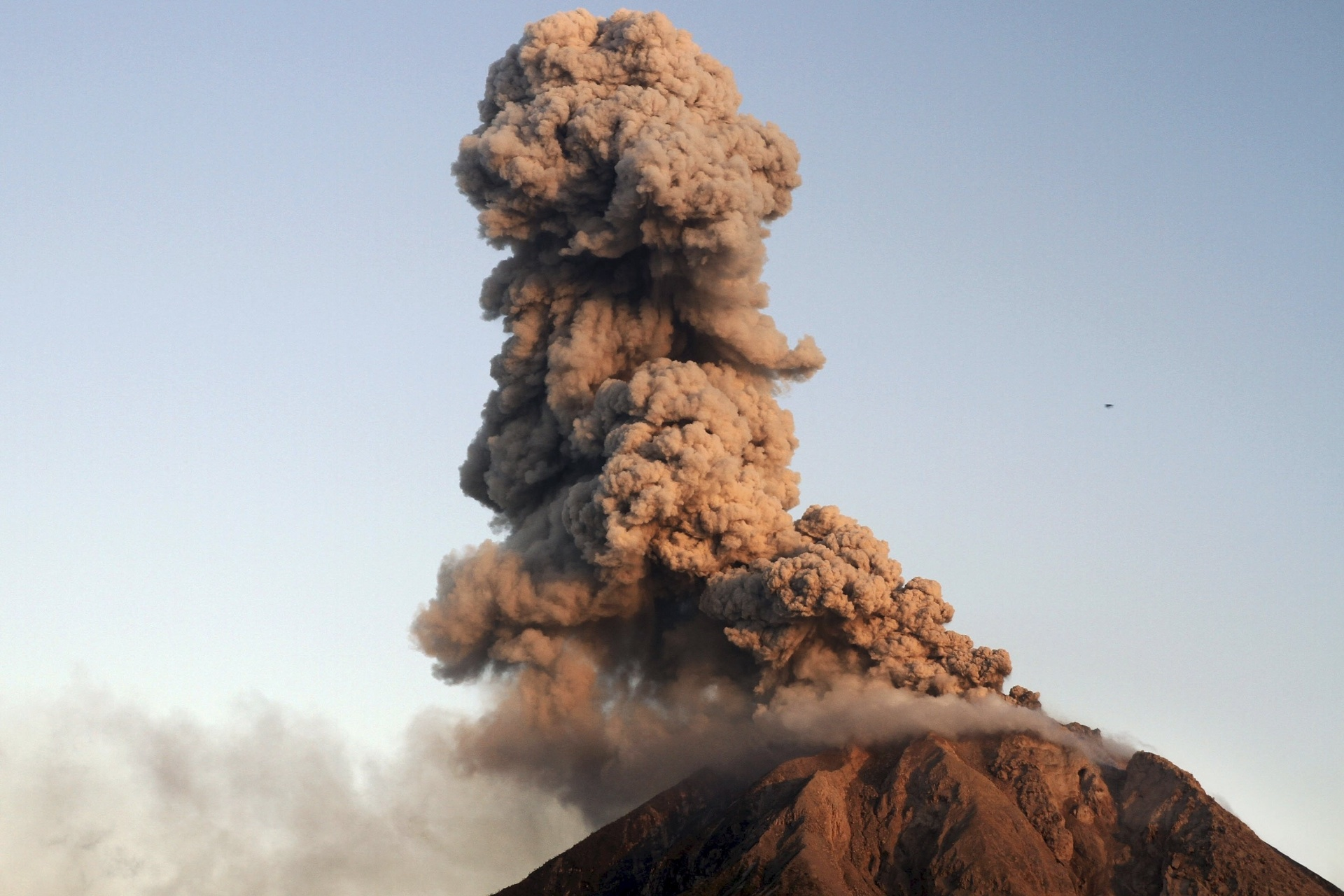 7.jan.2016 - Vulcão Sinabung expele cinzas durante erupção vista do vilarejo de Tiga Serangkai, no norte de Sumatra, na Indonésia