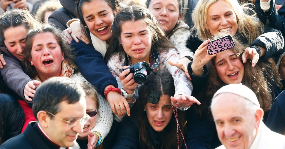 27.jan.2016 - Jovens choram ao ver o papa Francisco passar antes da audiência semanal na praça de São Pedro, no Vaticano