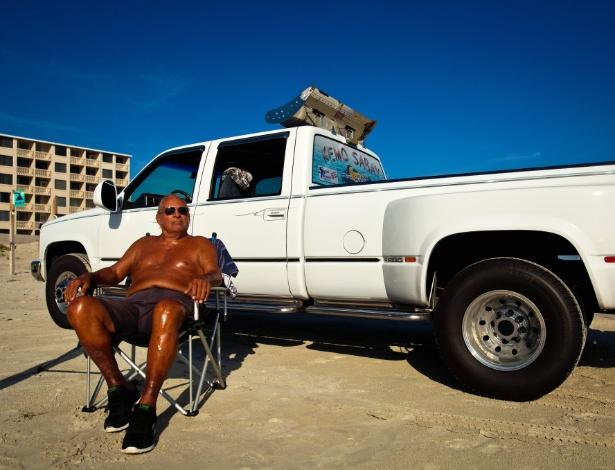 Ray Gramlich, defensor de que os moradores da Flórida (EUA) possam dirigir nas areias de Daytona Beach, toma sol perto de sua caminhonete na popular praia norte-americana