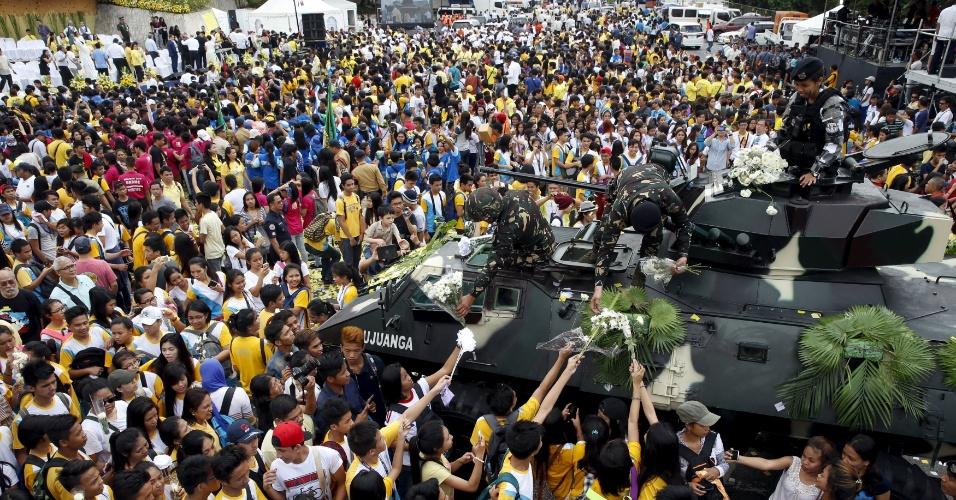 25.fev.2016 - Desfilando em um tanque de guerra na capital Manila, soldados recebem flores parada em celebração ao 30º aniversário da Revolução Popular das Filipinas, que tirou do poder o então presidente Ferdinand Marcos em 25 de fevereiro de 1986