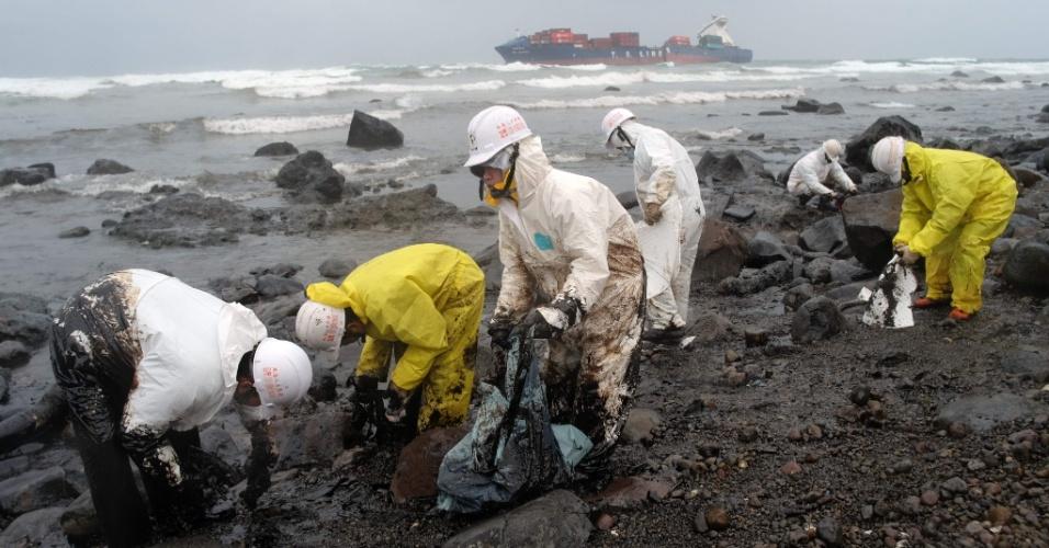25.mar.2016 - Trabalhadores removem de praia de Taipei (Taiwan) parte do óleo derramado do petroleiro T. S. Lines, visto ao fundo. A embarcação encalhou em um recife no início deste mês e a operação de resgate tem sido dificultada pelo mau tempo na região