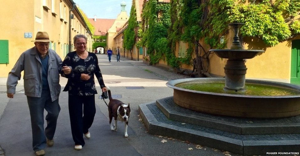 1º.out.2016 - Vizinhos Ilona Barber e Friedrich Fischer passeiam em Fuggerei, na cidade alemã de Augsburg