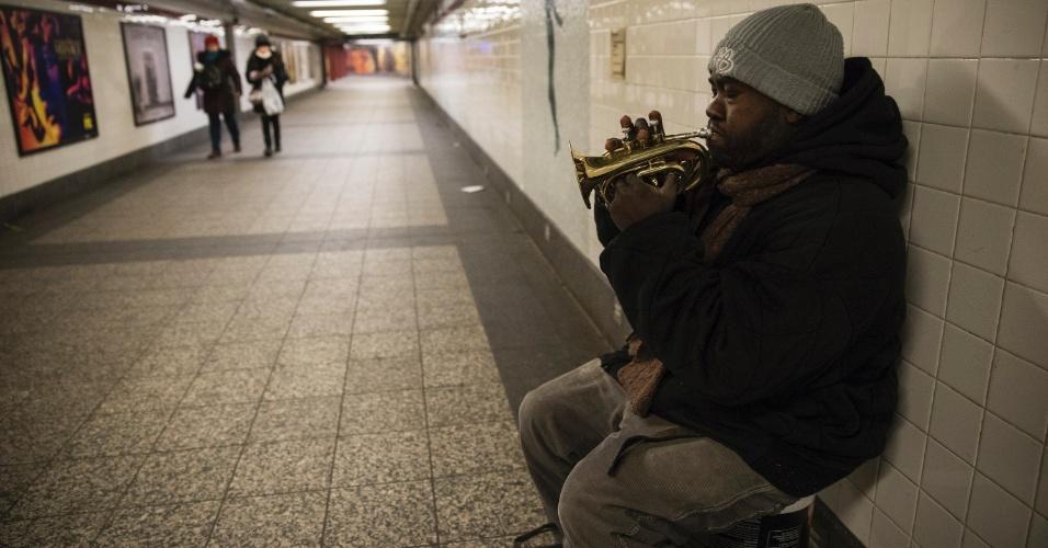 Jean, morador de rua, toca um pequeno trompete em estação de metrô em Nova York