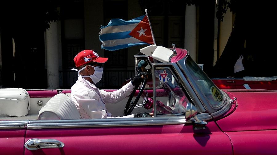 Taxista dirige carro americano antigo pelas ruas de Havana, em Cuba, com máscara no rosto para proteção contra o covid-19 - Yamil Lage/AFP