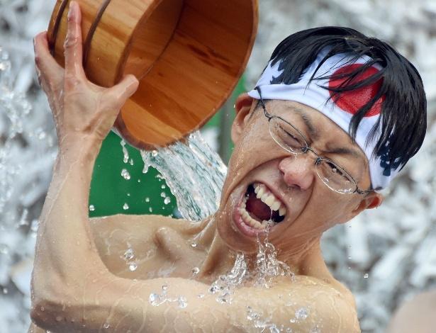 """9.jan.2016 - Japonês seguidor da crença Shinto joga água gelada sobre si mesmo em cerimônia para purificar o corpo e a alma realizada no Santuário de Kanda, conhecido como """"Kanda Myojin"""", em Tóquio. O evento faz parte das comemorações do Ano Novo no Japão"""