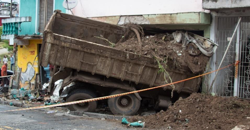 23.fev.2016 - Um caminhão carregado com terra bateu em uma Kombi e invadiu uma casa em Sapopemba, na zona leste de São Paulo, em acidente que deixou uma pessoa morta. O motorista do caminhão perdeu o controle do veículo quando fazia uma curva, bateu na Kombi, matando na hora seu condutor, e atingiu a casa. O caminhoneiro foi socorrido e encaminhado para um hospital da região