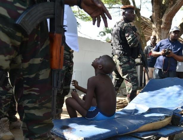 13.mar.2016 - Menino ferido é amparado por soldados após um atirador abrir fogo em hotel localizado na praia de Grand-Bassam, em Costa do Marfim. Ao menos 12 pessoas foram mortas