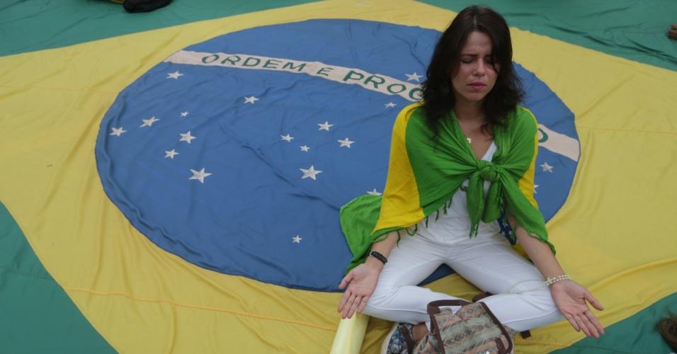 17.mar.2016 - Manifestante faz meditação em cima de bandeira gigante colocada na avenida Paulista, em São Paulo, durante protesto contra o governo Dilma Rousseff e o ex-presidente Luiz Inácio Lula da Silva