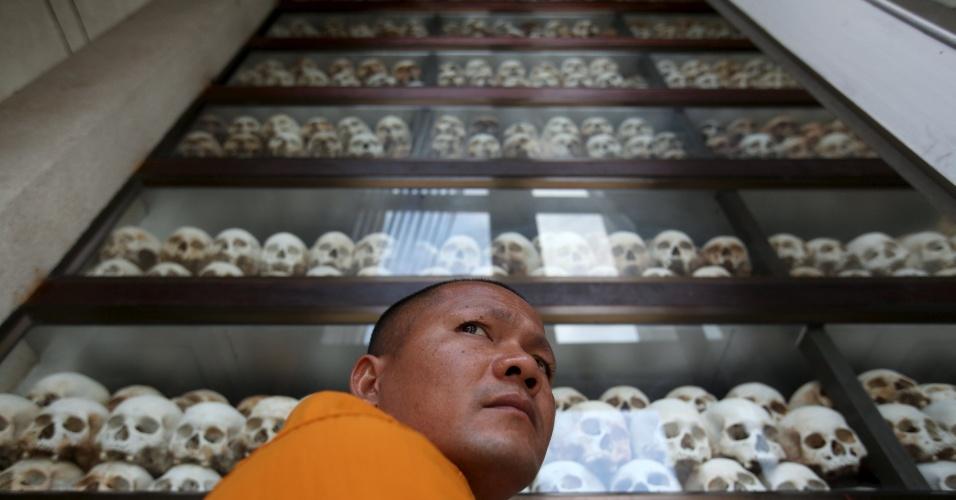 17.abr.2016 - Monge budista passa em frente a painel que exibe, na capital Phnom Penh, 5 mil crânios humanos de vítimas do genocídio empreendido pelo Khmer Vermelho, regime comunista que tomou o poder há 41 anos, em 17 de abril de 1975, e durou até janeiro de 1979