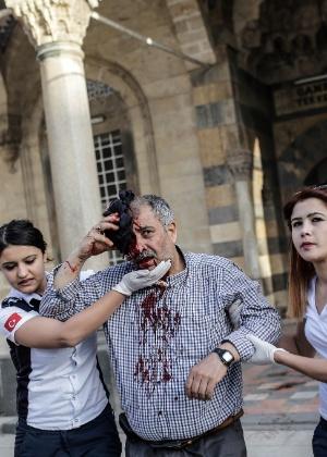 Equipe de resgate ajuda um homem ferido após um míssil atingir uma mesquita em Kilis, na Turquia