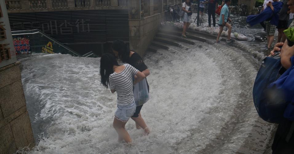 21.jul.2016 - Mulheres enfrentam enchente para tentar entrar em estação de trem em Tianjin, no nordeste da China. As fortes chuvas que castigam esta semana o norte do país deixaram pelo menos 14 mortos e 72 desaparecidos, segundo os escritórios de assuntos civis da região