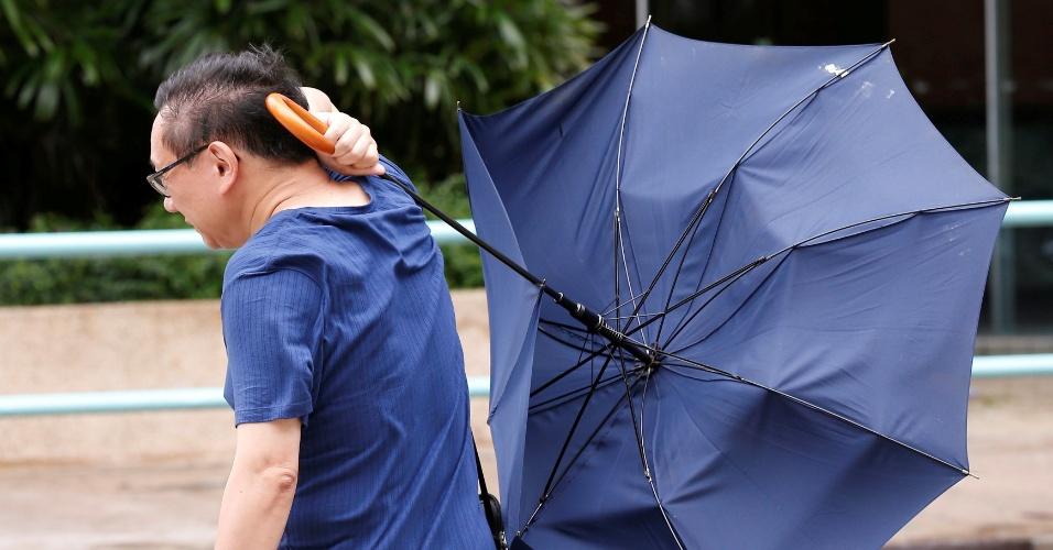 2.ago.2016 - Homem enfrenta os fortes ventos que antecedem a chegada do tufão Nida em Hong Kong, o primeiro da temporada e o mais potente em 30 anos. Devido à tormenta, que deve registrar ventos de até 151 km/h, autoridades chinesas pediram para a população das cidades em maior risco que armazenem alimentos em suas casas, além de outros itens de necessidades básicas suficientes para três dias