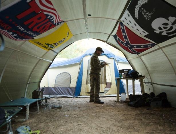 Membro da milícia III% toma café da manhã em barraca decorada com bandeiras da campanha de Donald de Trump e dos confederados, em Jackson (Geórgia)