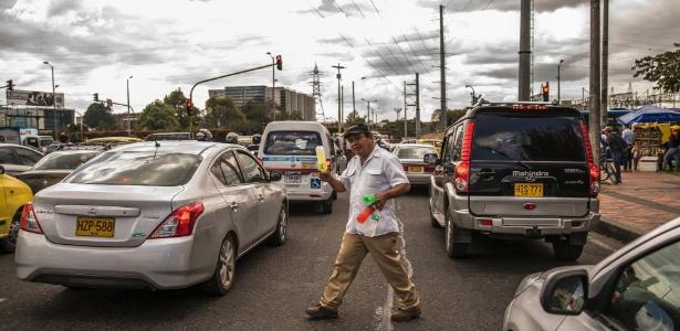 Vendedor ambulante oferece refrigerantes em semáforo de Bogotá, Colômbia