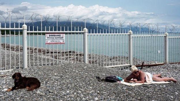 Uma mulher e um cachorro tomam banho de sol na fronteira entre Albecássia e Rússia