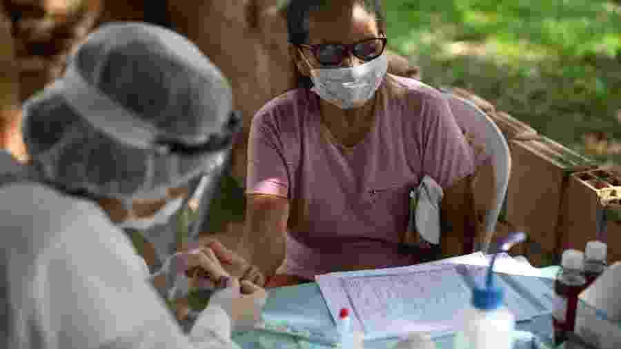 Profissional de saúde realiza teste para a doença covid-19 em uma mulher na Bela Vista do Jaraqui, às margens do rio Negro (AM) - BRUNO KELLY/REUTERS