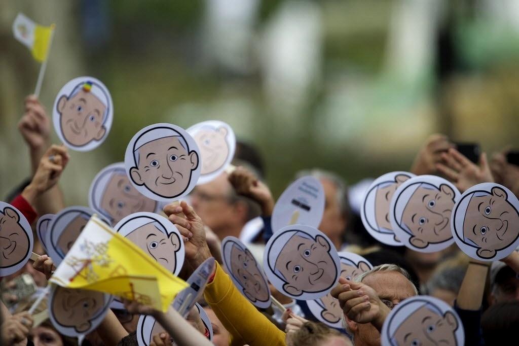26.set.2015 - Peregrinos erguem cartões com desenho do rosto do papa Francisco no lado de fora da Catedral Basílica de São Pedro e São Paulo, na Filadélfia (EUA), neste sábado (26). A Filadélfia é a última etapa da viagem de seis dias do pontífice pelos Estados Unidos
