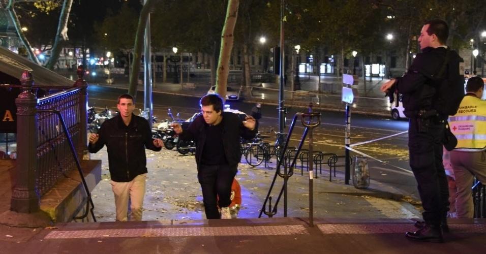 13.nov.2015 - Homens são evacuados da praça da República, em Paris, na França, após uma série de ataques ocorridos na capital francesa. Tiroteios e explosões aconteceram na noite desta sexta-feira (13) na capital francesa. A polícia relatou ao menos duas explosões nas proximidades do estádio Stade de France, onde o presidente francês, François Hollande, acompanhava um amistoso da seleção francesa