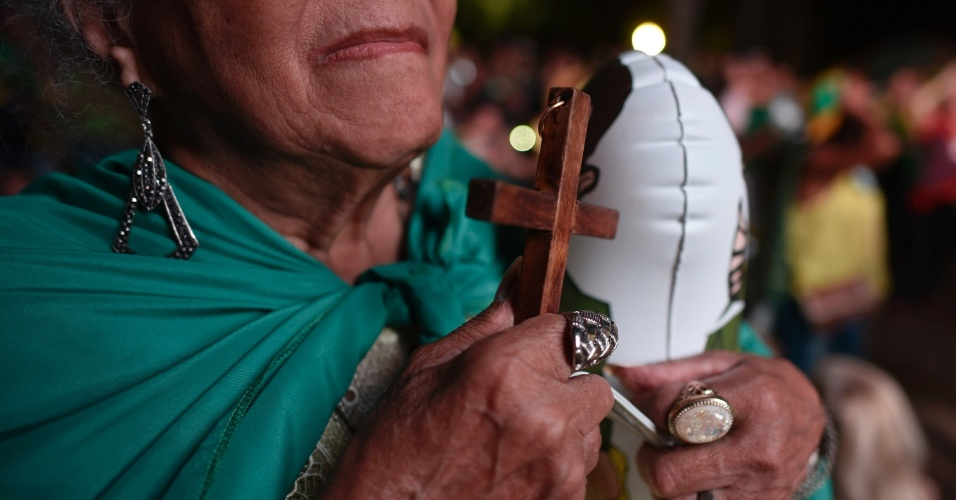 17.abr.2016 - Manifestante a favor do processo de impeachment da presidente Dilma Rousseff segura um crucifixo durante ato na praça da Liberdade, em Belo Horizonte (MG), enquanto acompanha a votação na Câmara