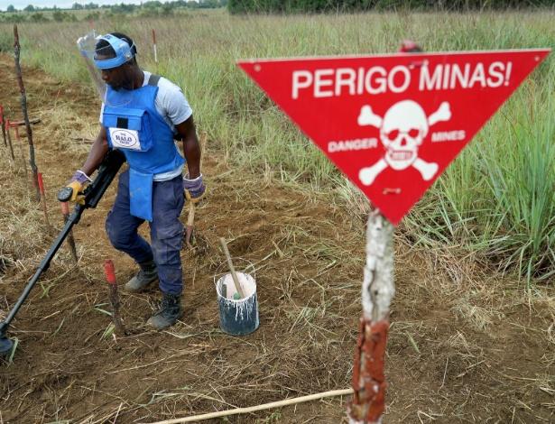 Lino Domingos, usando um detector de metais para localizar mina terrestre no solo em Humabo, Angola