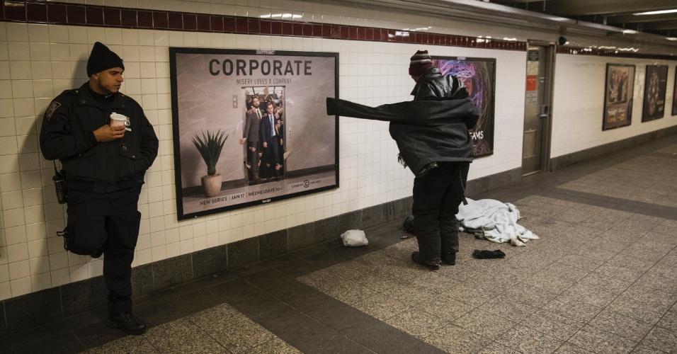 Policial observa homem que se levanta em estação de metrô de Nova York