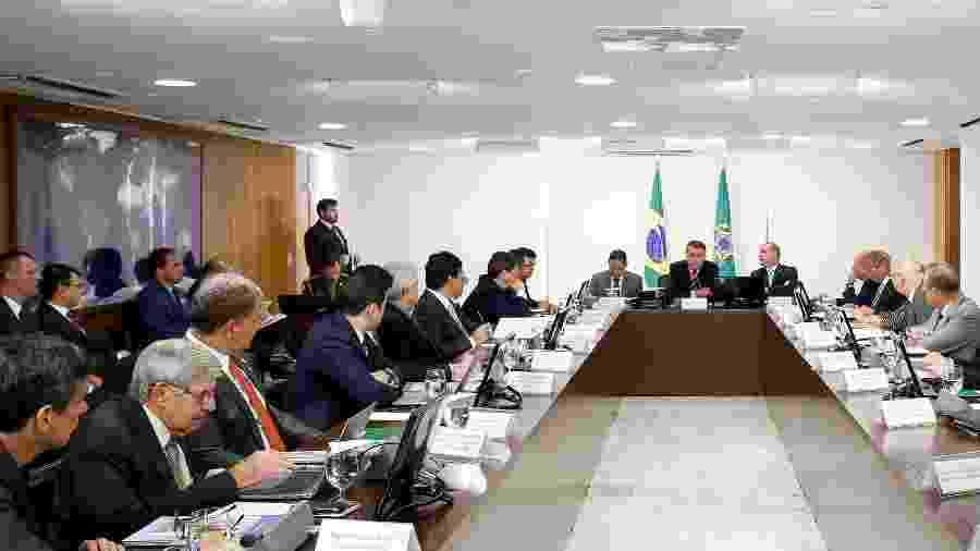 15.jan.2019 - Carlos Bolsonaro (à esquerda, de terno azul) acompanha reunião do presidente Jair Bolsonaro com seus ministros no Planalto - Alan Santos/PR