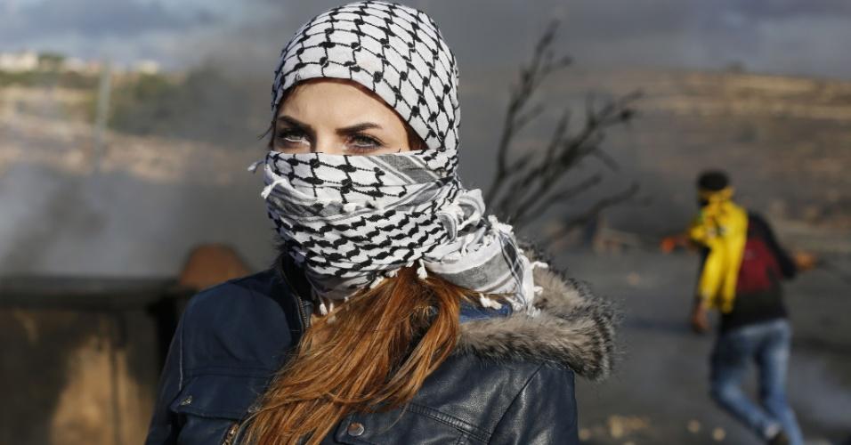 30.out.2015 - Estudante palestina da Universidade Birzeit cobre o rosto com o keffiyeh xadrez tradicional durante confrontos entre estudantes e soldados israelenses na cidade palestina de Al-Bireh, aos arredores de Ramallah, na Cisjordânia