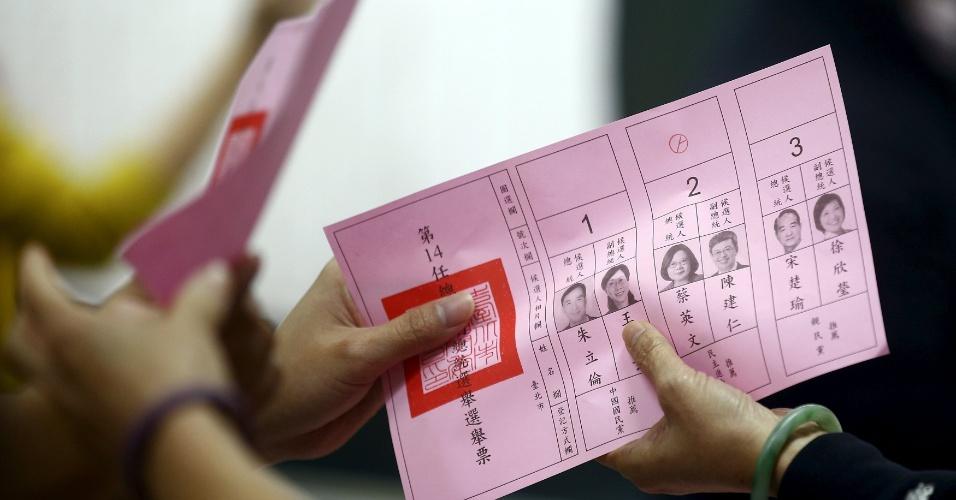 16.jan.2016 - Taiwanês entrega cédula em papel com voto na chapa do PDP (Partido Democrata Progressista) na eleição presidencial do país, realizada neste sábado. O pleito pode provocar uma mudança radical na política interna e nos laços com a China, já que o PDP, de caráter independente, é favorito para assumir o comando do país