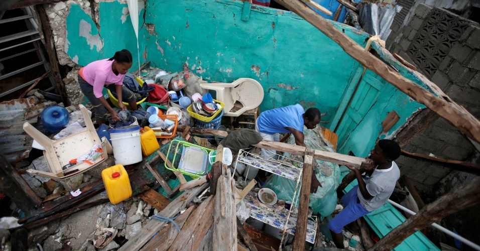 5.out.2016 - Moradores tentam limpar o que restou de casa localizada em Les Cayes, no Haiti, destruída pelo furacão Mathew