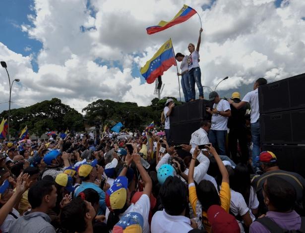Lilian Tintori (á dir.), mulher do líder da oposição venezuelana Leopoldo Lopez, que está preso, e a ex-deputada Maria Corina Machado seguram a bandeira da Venezuela durante protesto em Caracas