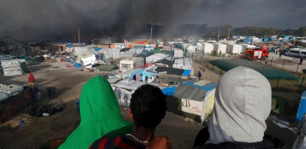 Imigrantes observam incêndio de barracas no acampamento de Calais, na França