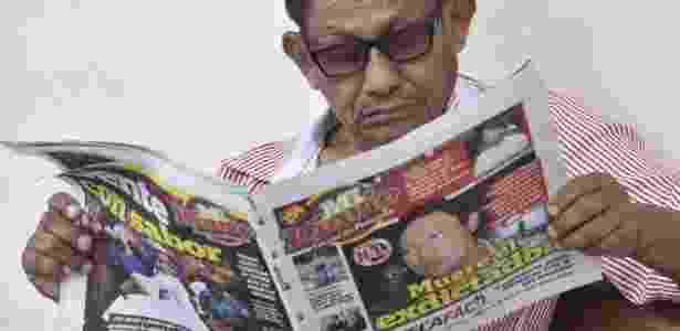 Homem lê jornal com notícia sobre a morte do ex-ditador manuel Noriega, na Cidade do Panamá - Rodrigo Arangua/AFP