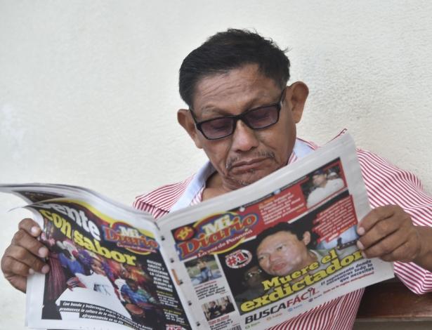 Homem lê jornal com notícia sobre a morte do ex-ditador manuel Noriega, na Cidade do Panamá