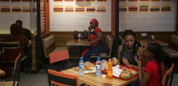 Mulheres comem em um Burger King no shopping The Hub, repleto de redes de fast food norte-americanas, em Nairóbi, no Quênia