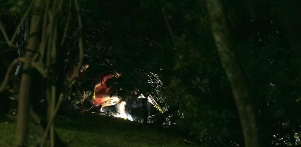 Policiais fazem perícia no local onde foi encontrado o cadáver de uma mulher de 25 a 30 anos