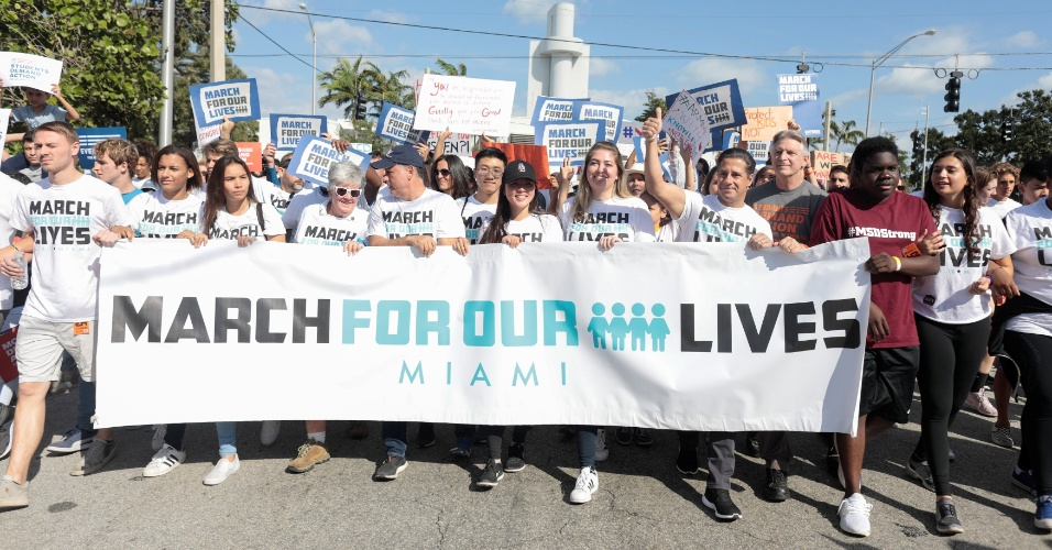 """24.mar.2018 - Manifestantes carregam faixa com a frase """"Marche por nossas vidas"""" em Miami, nos EUA, pedindo leis mais severas em relação ao controle de armas"""
