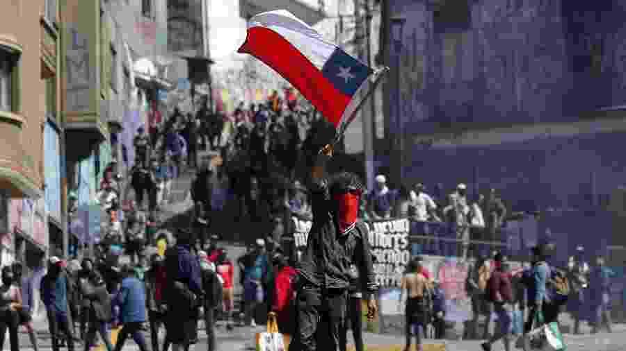 21.out.2019 - Manifestante mascarado ergue bandeira do Chile em meio aos protestos em Valparaíso, na região costeira do país - Javier Torres/AFP