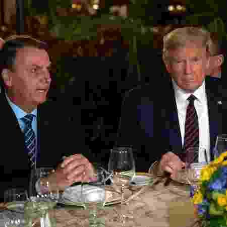 O presidente do Brasil, Jair Bolsonaro, e o presidente dos EUA, Donald Trump, durante jantar na Flórida - Jim Watson/AFP