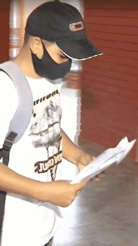 Lorran com as lições em mãos, após buscá-las no colégio - Reprodução/TV Anhanguera - Reprodução/TV Anhanguera
