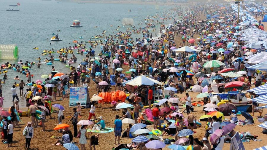 Durante onda de calor em 2015, banhistas se refrescaram na praia de Jinshitan, em Dalian, nordeste da China - Song Weixing/Xinhua