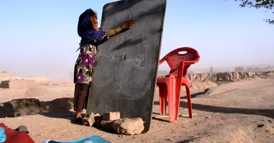 3.out.2015 - Estudante escreve em lousa durante aula em escola ao ar livre em Jalalabad, leste do Afeganistão. Cerca de 3,5 milhões de crianças afegãs, de acordo com a Unicef, estão fora da escola, embora o país tenha feito grandes conquistas no campo da educação nos últimos 14 anos