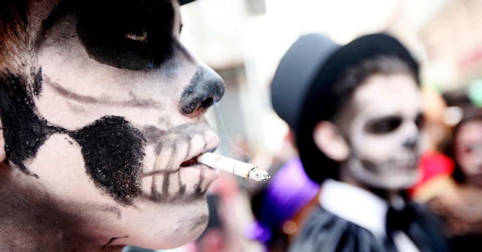 2.nov.2015 - Homem com o rosto pintado de caveira caminha pelo centro de São Paulo enquanto fuma um cigarro. A Zombie Walk acontece desde 2006 em São Paulo, no Dia de Finados